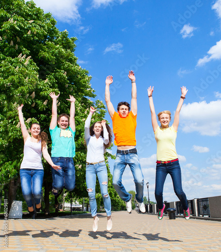 Photo  Group of smiling teenagers jumping outdoors