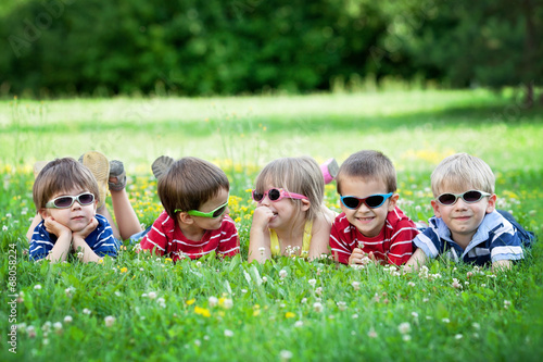 Photo  Five adorable kids, lying on the grass, smiling, having fun
