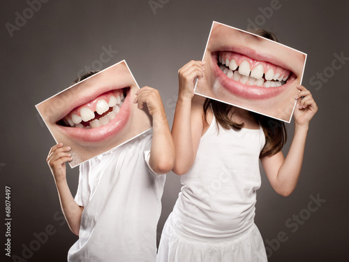 Plakat two children holding a picture of a mouth smiling