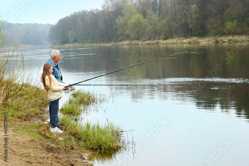 Printed kitchen splashbacks Fishing Grandfather and granddaughter are fishing