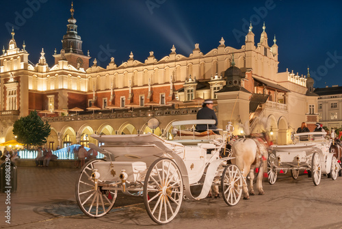 Fotobehang Krakau Carriages before the Sukiennice on The Main Market in Krakow