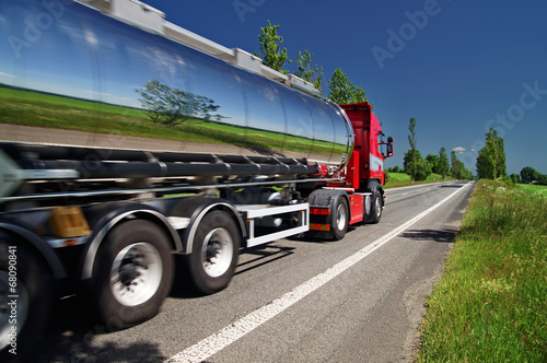 Photo  Mirroring the landscape chrome tank truck moving on a highway