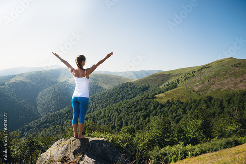 Fényképezés  Young woman meditate on the top of mountain