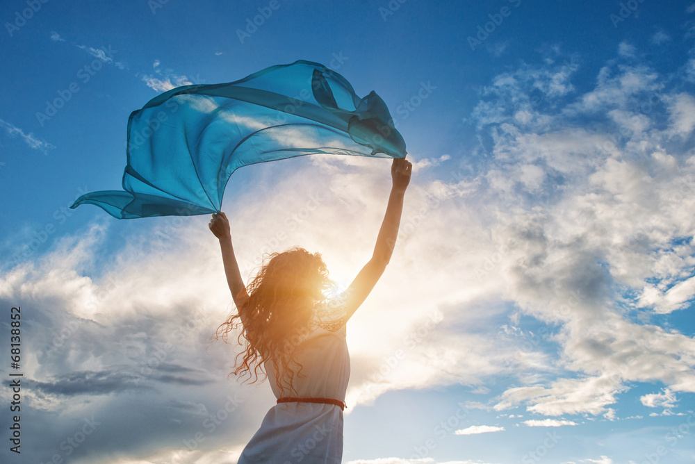 Fototapeta Beautiful young woman holding blue scarf on the wind