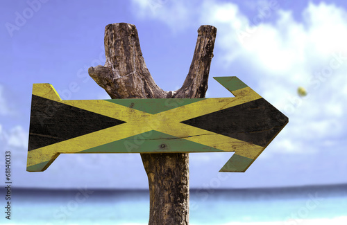 Foto  Jamaica wooden sign with a beach on background