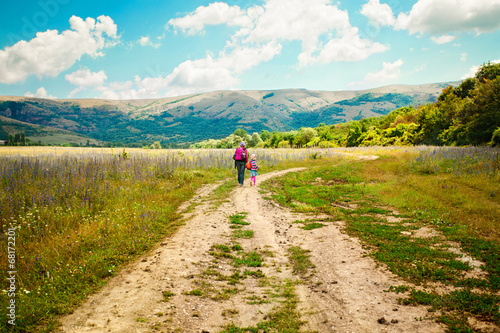 Fotografia, Obraz  Mother and daughter walk on road through field