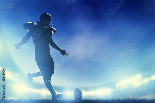 Photo American football player kicking the ball, kickoff