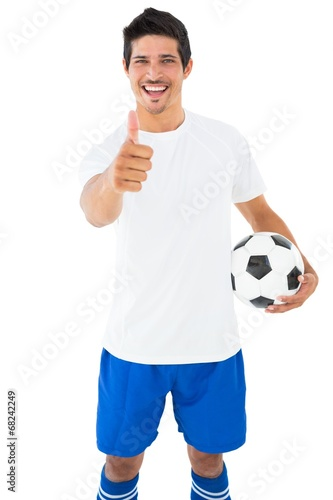 Football player in white holding ball showing thumbs up