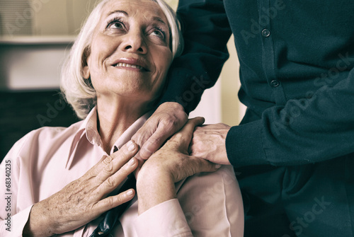 Fotografie, Obraz  Senior woman on wheelchair taking her husband's hand