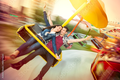 Fotobehang Amusementspark Young happy couple having fun at amusement park