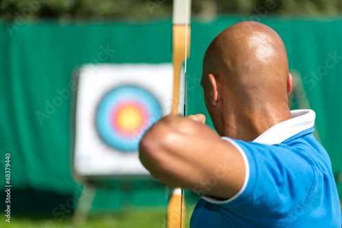 Archer aiming at target with bow and arrow Canvas Print