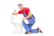 Smiling plumber trying to fix a toilet