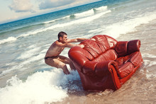 Man Dragging Vintage Sofa Into Sea