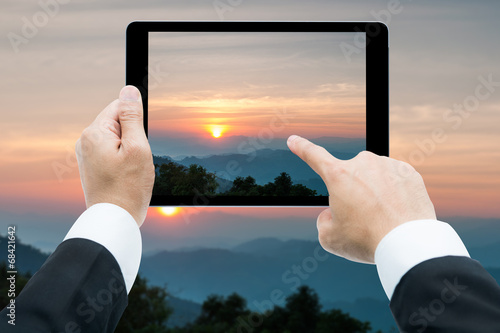 City on the water Businessman hands tablet taking pictures Majestic sunset in the