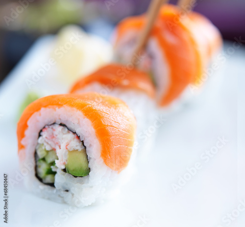 colorful salmon japanese sushi being picked up with chopsticks Canvas Print