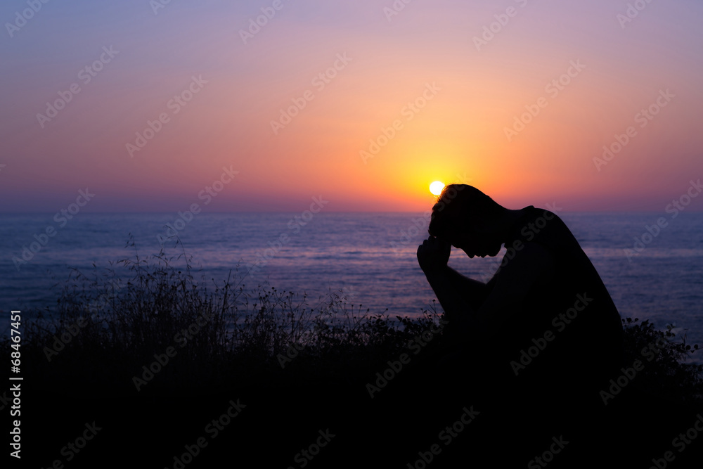 Fototapety, obrazy: Man Praying by the Sea at Sunset
