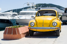 Retro Yellow Car With Luxury Yachts On Background