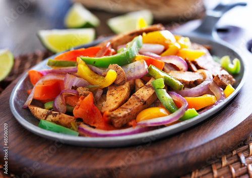 Foto mexican chicken fajitas in iron skillet with peppers