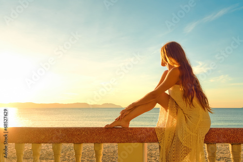 Foto  A woman on a balcony looking at the beautiful sunset