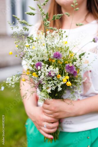 Fototapeta Woman holding wild flowers obraz na płótnie