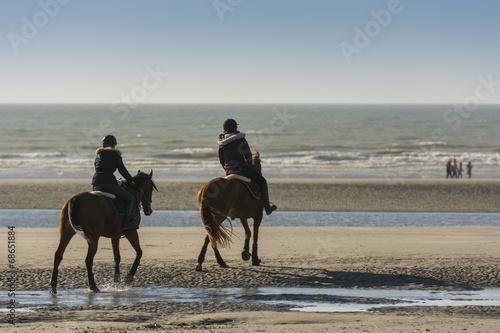Photo  Cavaliers et leurs chevaux sur la plage en train de marcher et d