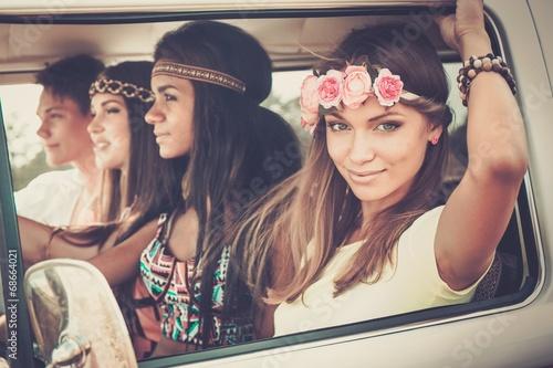 Photo  Multi-ethnic hippie friends in a minivan on a road trip