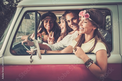 Fotografía Multi-ethnic hippie friends in a minivan on a road trip