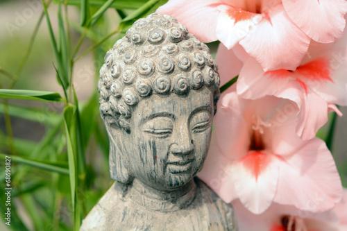 Foto auf Gartenposter Blumenhändler Boeddha in bamboe tuin met bloemen