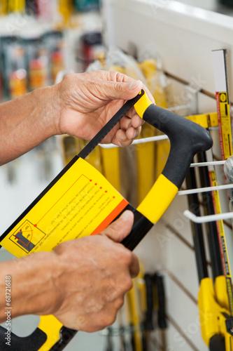 Fotografie, Obraz  Salesman Examining Hacksaw In Store