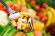 Leinwandbild Motiv spoon with dietary supplements on fruits background