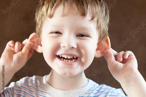 Photo  Happy Little boy, pulling himself on the ears