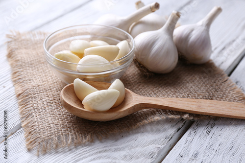 Fotografía  Fresh sliced garlic in glass bowl on wooden background
