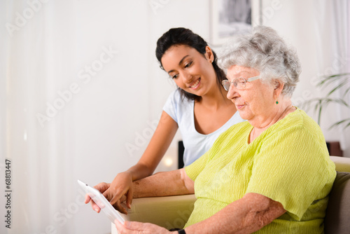 Fotografía  cheerful young girl with elderly woman playing with tablet home