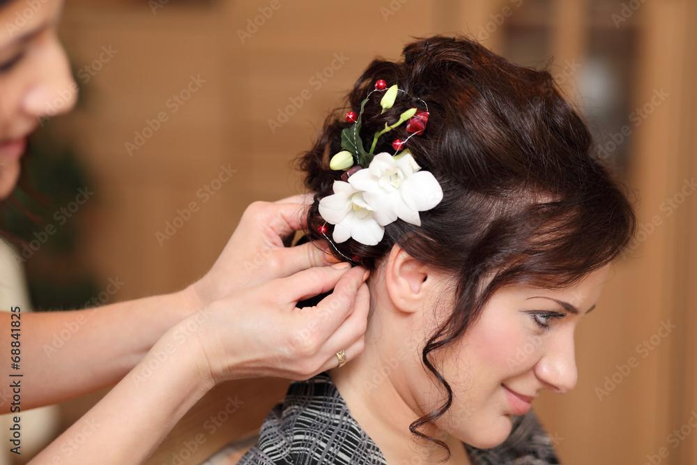 Fototapeta Fryzjerka wpina kwiat we włosy dziewczyny.