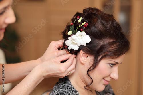 Fototapeta Fryzjerka wpina kwiat we włosy dziewczyny. obraz