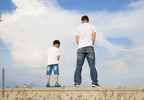 father and son standing on a stone platform and pee together Canvas Print