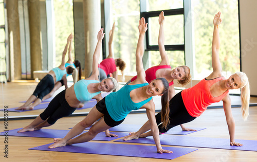 Photo  smiling women meditating on mat in gym