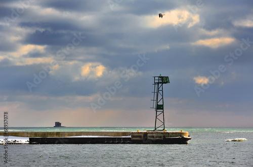 Fotobehang - Morze Bałtyckie , krajobraz zimowy z latarnią morską