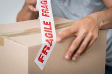 Man Sealing Box With Fragile Adhesive