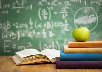 Fototapeta samoprzylepna School books with apple on desk