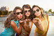 Three stylish girlfriends in sunglasses send air kiss to camera