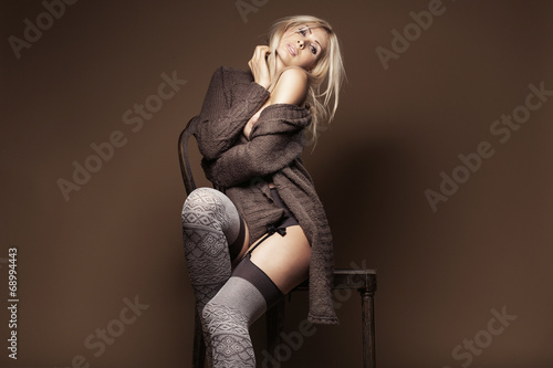 Fotografía  Beautiful blond wearing cardigan and stockings on the chair