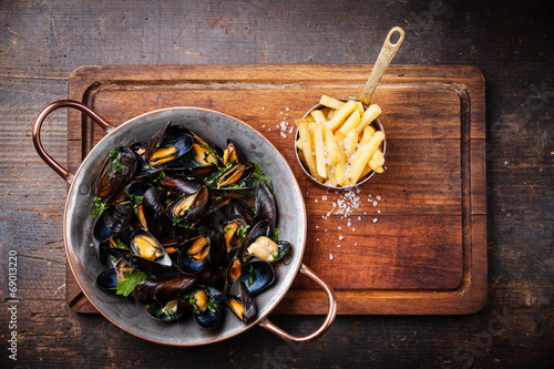 Valokuva  Mussels in copper cooking dish and french fries on dark wooden b