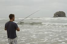 Man Fishing In The Surf On Rockaway Beach