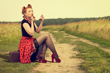 Woman  Sitting On The Side Of A Rural Road Painting Lipstick.