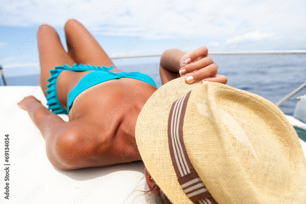 Fototapety, obrazy: Attractive girl sunbathing on a yacht holding her hat