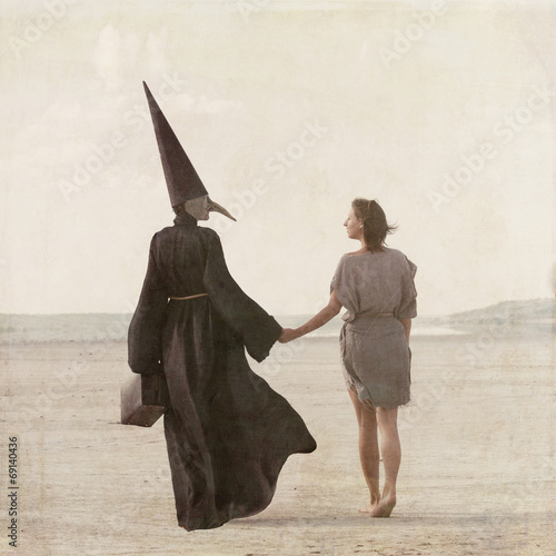 Photo  Woman and person in plague mask walking away through desert