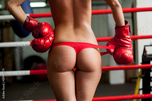 Elastic female boxer's ass in red thongs, close-up - 69148279
