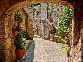 FototapetaArched cobblestone street in a Tuscan village, Italy
