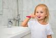 Girl brushing her teeth in the bathroom